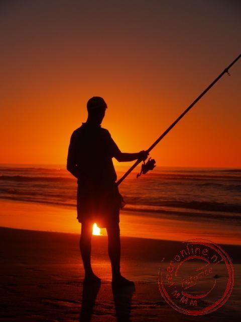 Een visser op het strand van Sidi Ifni met de zonsondergang