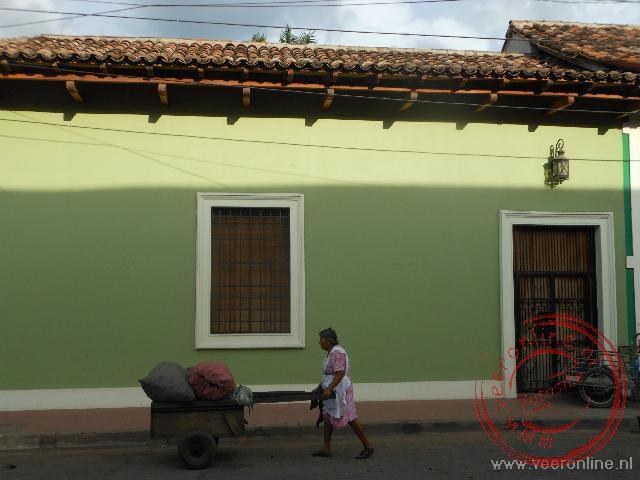 Een vrouw passeert een gekleurd huisje in Granada