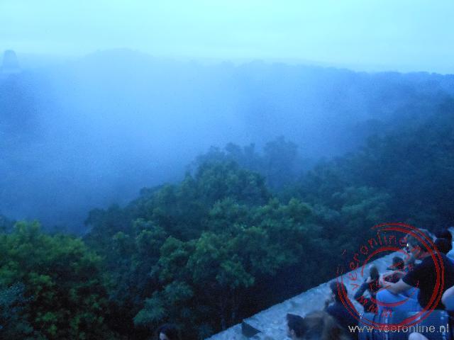 Uitzicht over het oerwoud van Tikal bij zonsopkomst