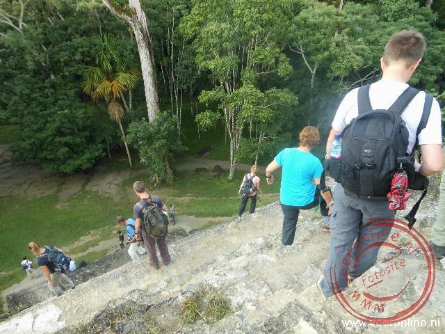 Voorzichtig afdalen van de steile tempel in Tikal