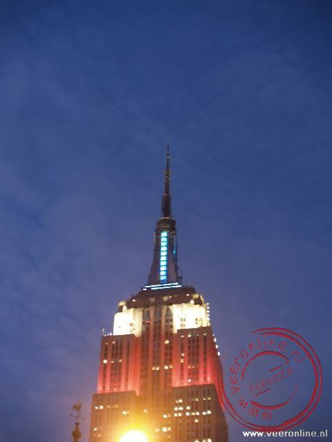 De top van het Empire State Building fraai verlicht