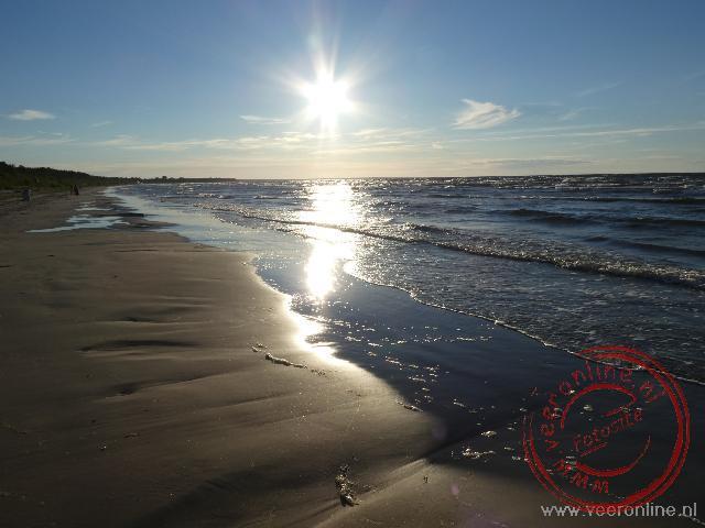 De zon gaat onder bij het strand aan de baai van Riga