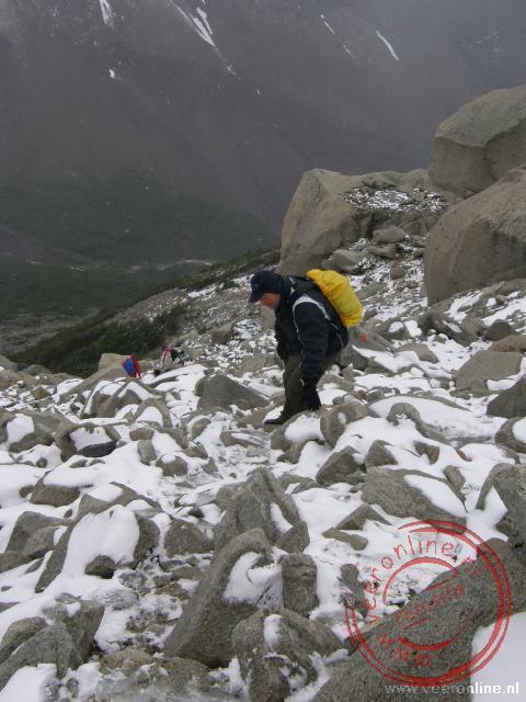 Het is voorzichtig klimmen over de rotsblokken door de sneeuw