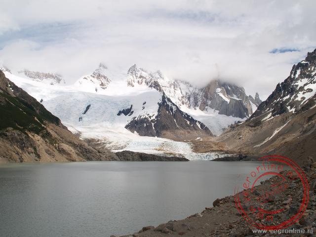 De Glaciers Grande stroomt langzaam in de Laguna Torre. Op de achtergrond is de Cerro Torre in de wolken verdwenen