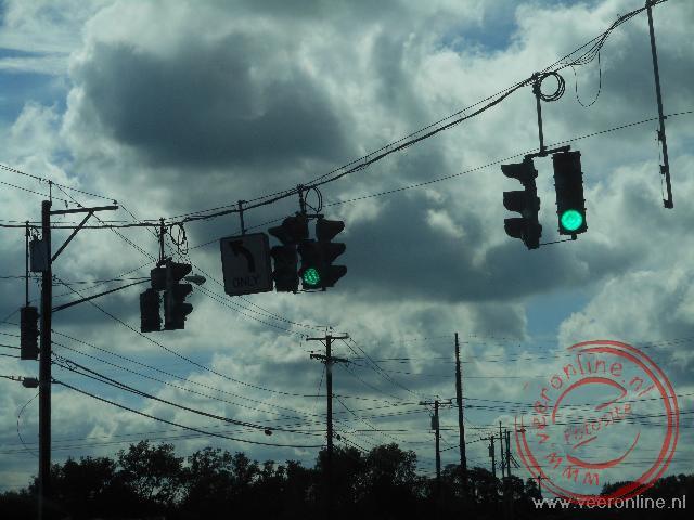De verkeerslichten hangen aan een kabel boven het kruispunt