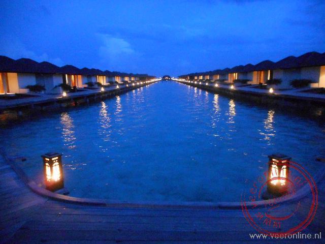 De sfeervolle verlichting van de watervillas bij avond