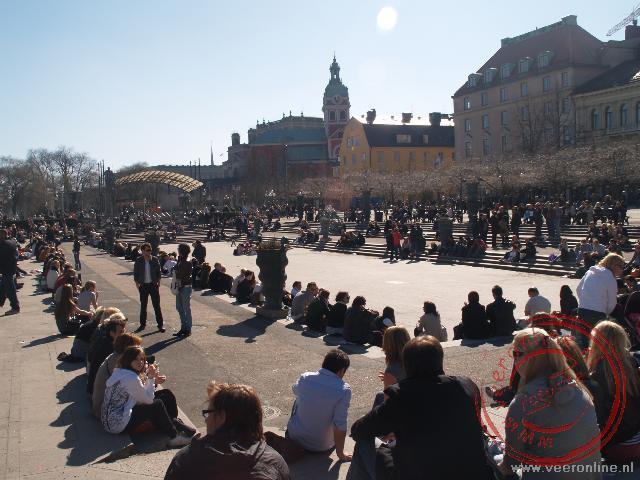 Veel mensen genieten van de zon in het stadspark