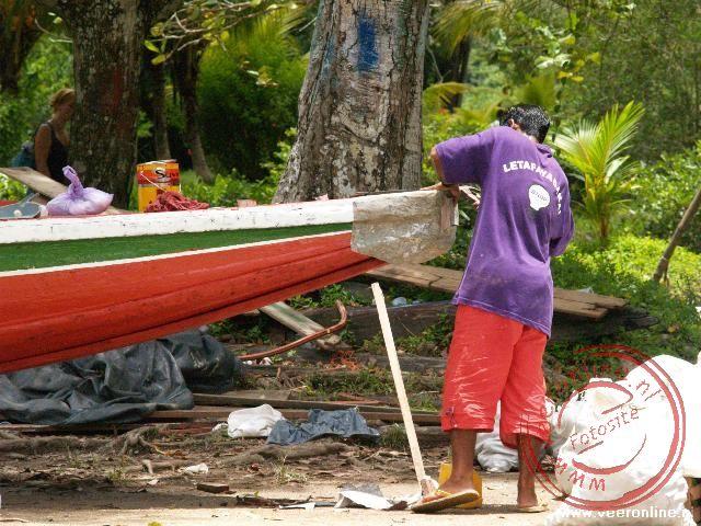 Het onderhoud aan de korjaal, de boot die gebruikt wordt op de rivier