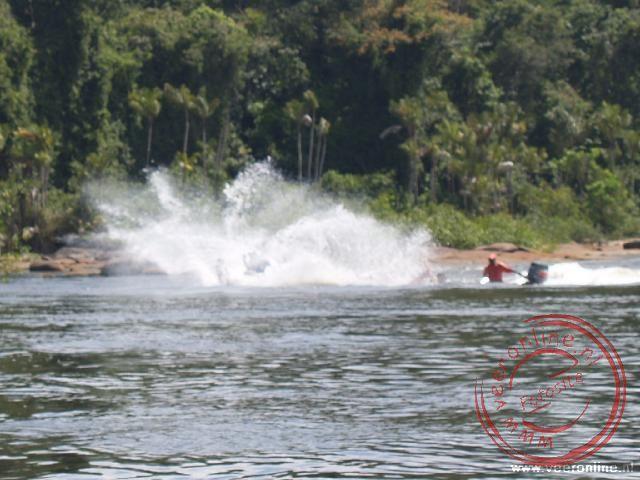 De korjaal vaart met hoge snelheid tegen de stroomversnelling op