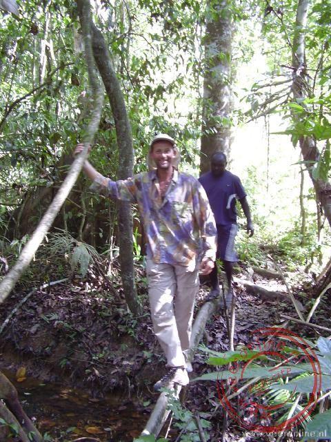 Jan steekt de beek over over een smalle boomstam