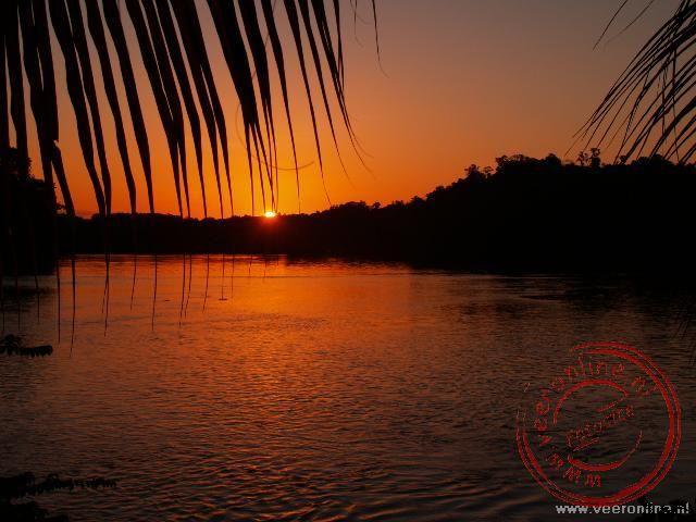 De prachtige zonsondergang op de Tapanahonie rivier