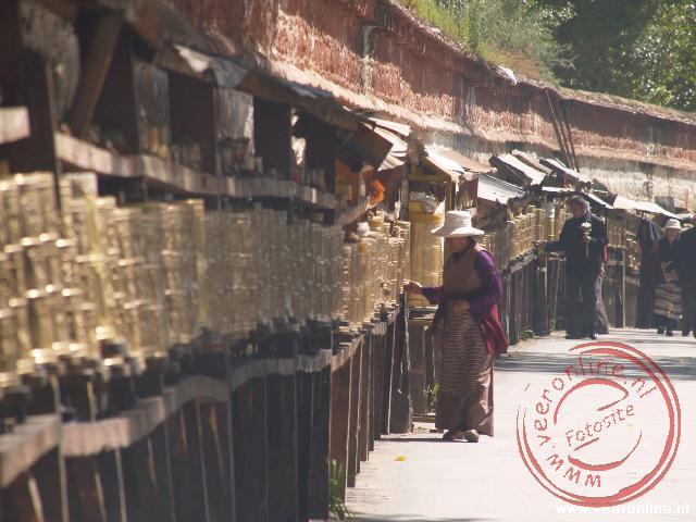 Een pelgrim loopt de kora langs de gebedsmolens
