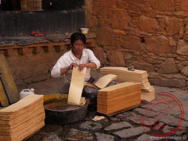 Het papier wordt gwassen, sneden en bedrukt voor de monniken