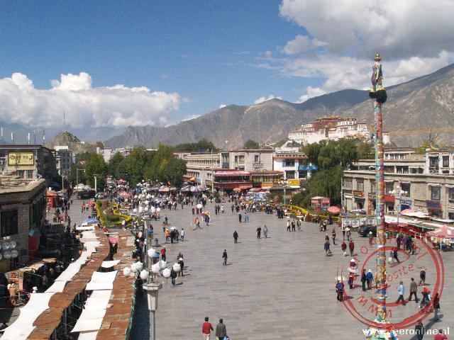 Het Barkhor Square gezien vanaf het dak van de Jokhang. Op de achtergrond staat het Potala paleis