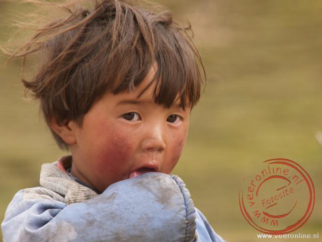 Een jongentje langs de kant van de weg nabij Tidrum
