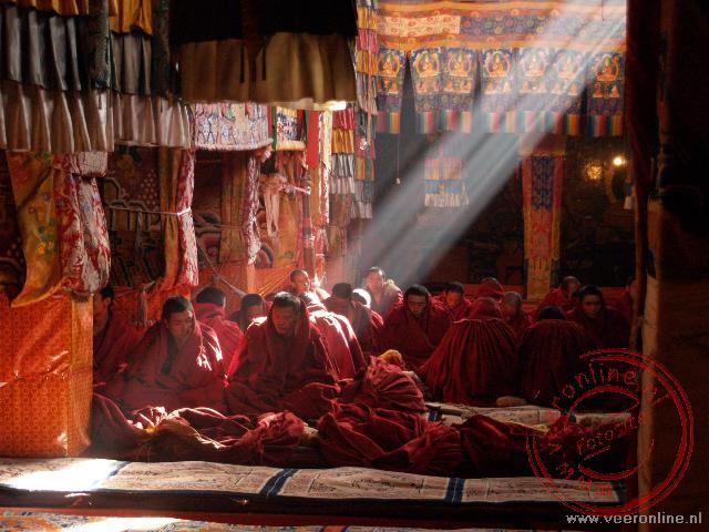 Monniken bidden in een straal zonlicht in het Ganden Klooster