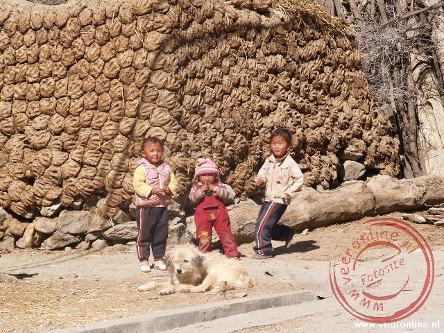 Kinderen spelen op straat in Gyantse voor de muur beplakt met Yak-uitwerpselen