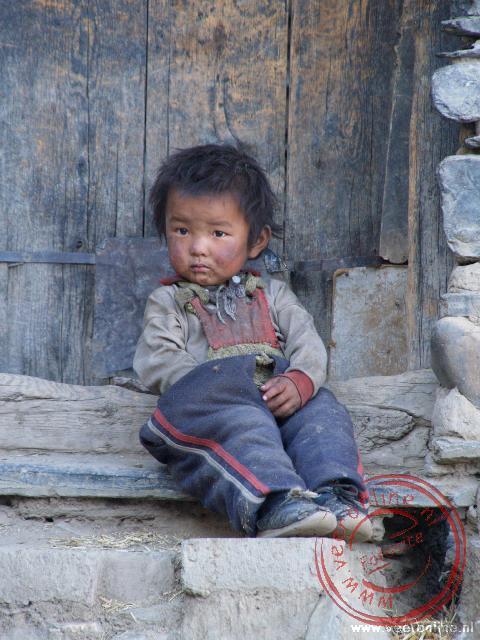 Een jongetje zit op de stoep in Shegar