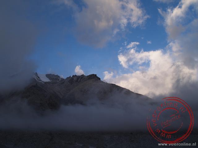 De bergtoppen, wolken en de opkomende zon aan de flanken van de Mount Everest