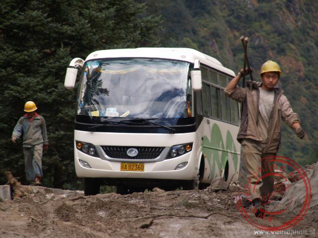 De bus werkt zich tussen de werkzaamheden door over de toch al niet brede weg