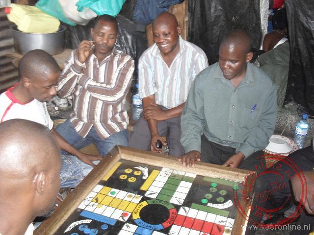 Mannen spelen een spelletje op de markt van Kampala