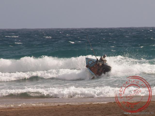 Vissers proberen tevergeefs hun boot door de branding te krijgen. Ze worden teruggeworpen door de zee.