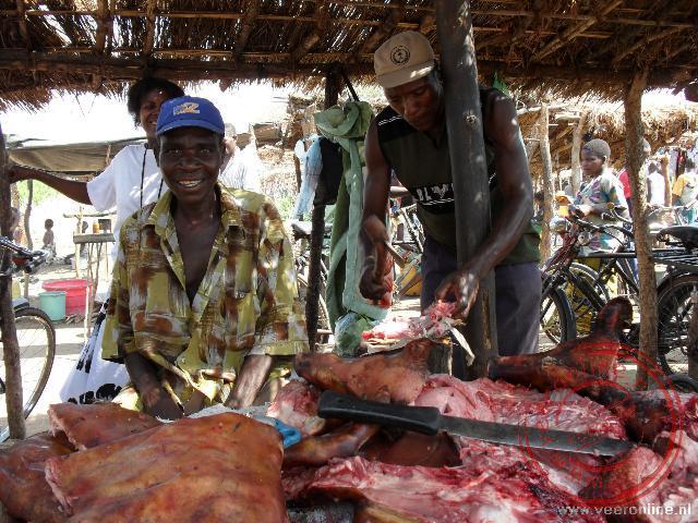 De slager hakt zijn vlees op de lokale markt in Mozambique