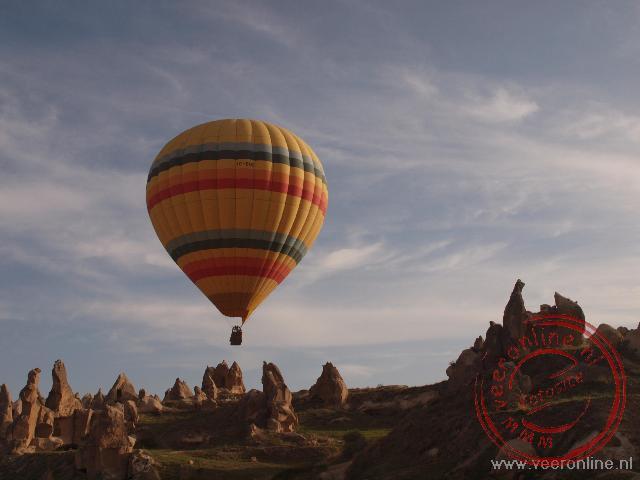 De luchtballon gaat vlak over de rotsen in Cappadocië