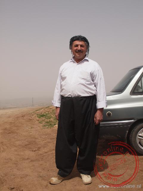 Een man toont zijn Koerdische kledij