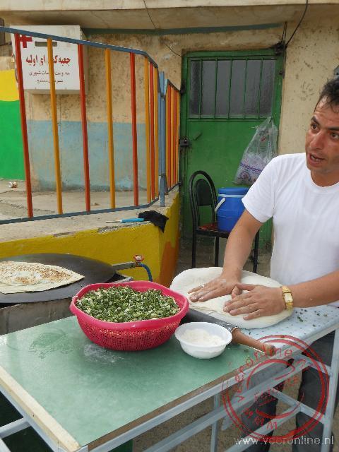 In een kraampje in het park wordt een brood-pannenkoek met groente klaar gemaakt