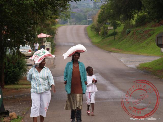 Zuid Afrikaanse vrouwen wandelen door het gouddelversplaatsje Pelgrims Rest