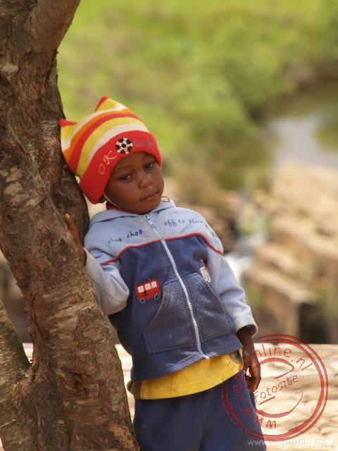 Een jongetje kijkt aarzelend naar de vele toeristen