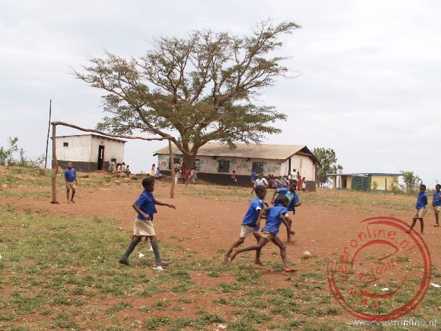 Kinderen spelen voetbal op het schoolplein