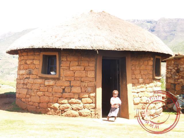 Een meisje staat in de deuropening in Malealea